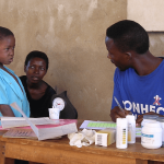 A community health worker listens to his patient